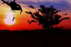 Soldatschattenbild, beim rappelling klettern unten vom Hubschrauber auf Sonnenuntergang mit Kopienraum addieren Text Stockfotografie