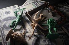 Soldatspielwaren mit Mäusefalle auf Geld Stockbilder