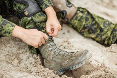 Soldatstiefel und -hände, die Schnürsenkel in der Wüste binden stockfotografie