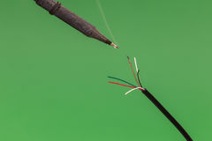 Soldering a copper wire on green background Royalty Free Stock Images