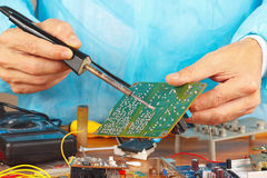 Soldering electronic board of device in service workshop Royalty Free Stock Photography