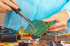 Soldering electronic board in service workshop Stock Photos