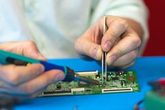 Soldering of electronic smd-components with a soldering iron with ceramic heater and adjustable temperature closeup. Soldering of electronic smd-components with Royalty Free Stock Images
