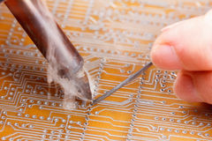 Soldering iron and circuit board Stock Photos