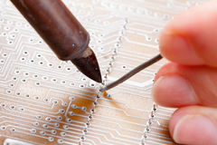 Soldering iron and circuit board Royalty Free Stock Image