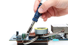 Soldering iron in hand and electric board. Stock Photo