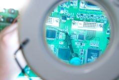 Soldering iron in magnifying glass. Repair of a green circuit board seen through a magnifying glass. A person is soldering a component to the board Royalty Free Stock Images