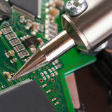 Soldering iron and microcircuit Stock Images