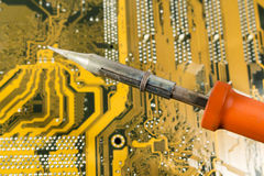 Soldering iron with red handle over a printed circuit board Royalty Free Stock Photography