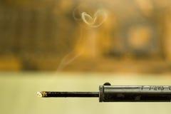 Soldering iron with smoke. Closeup of heated soldering iron with smoke on blurred background Royalty Free Stock Photo