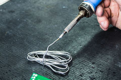 Soldering iron and solder in the hands of a man Royalty Free Stock Photo