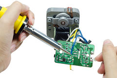 Soldering iron with tin on a motor circuits. Royalty Free Stock Photography