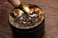 Soldering iron tip and solder flux close up. On wooden table royalty free stock photography
