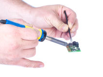 Soldering microchip. Two male hands. In his left hand man holding a microchip in the right hand man holding a soldering iron. Isolated white Royalty Free Stock Image