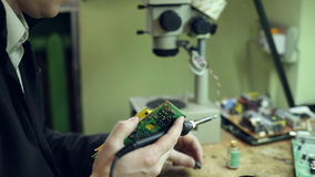 Soldering pads on the device. Scientist soldering pads on the device stock footage