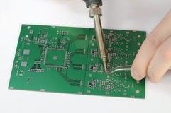 Soldering resistor to printed circuit board. With tweezers stock image