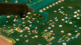 Soldering with tin on the electronic board. Working in the electronic board, close-up stock video footage