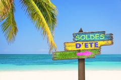 Soldes d`ete meaning summer sale in French written on pastel colored wood direction signs, beach and palm tree background. Soldes d`ete meaning summer sale in Stock Photos