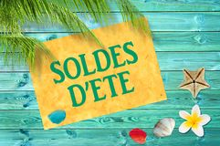 Soldes d`ete meaning summer sale in French written on yellow sign, blue wood planks, seashells, beach and palm tree backgroun royalty free stock photo