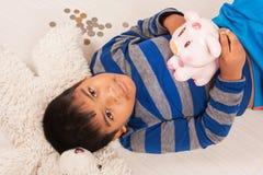 Soldi asiatici di risparmio del ragazzo in porcellino salvadanaio Fotografia Stock