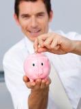 Soldi attraenti di risparmio dell'uomo d'affari in un piggybank Fotografia Stock
