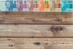 Soldi brasiliani tutte le denominazioni sui precedenti di legno con il posto per un testo Fotografia Stock
