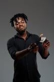Soldi brucianti del giovane riuscito uomo d'affari africano sopra fondo scuro fotografia stock libera da diritti