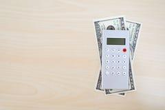Soldi, calcolatore, matita e taccuino in bianco su fondo di legno, Fotografie Stock