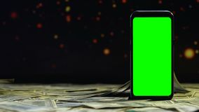 Soldi che cadono sulla tavola intorno allo smartphone verde dello schermo, guadagni su Internet stock footage