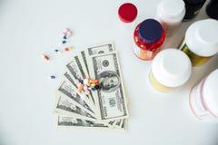 Soldi con le pillole e le vitamine Fotografie Stock Libere da Diritti