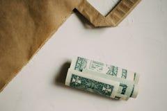 Soldi dei dollari dei contanti, con un pacchetto di Kraft su fondo bianco fotografie stock
