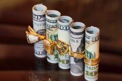 Soldi dei rotoli delle banconote in dollari con gli anelli dei gioielli dell'oro Fotografia Stock