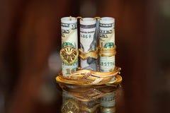 Soldi dei rotoli delle banconote in dollari con i gioielli dell'oro Immagini Stock