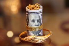 Soldi dei rotoli delle banconote in dollari con i gioielli dell'oro Immagine Stock