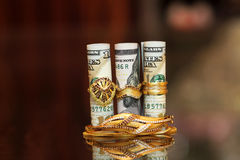 Soldi dei rotoli delle banconote in dollari con i gioielli dell'oro Fotografia Stock Libera da Diritti