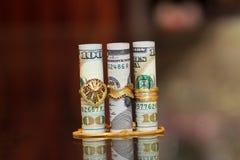 Soldi del rotolo delle banconote in dollari con i gioielli dell'oro Fotografia Stock