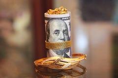 Soldi del rotolo delle banconote in dollari con i gioielli dell'oro Fotografie Stock Libere da Diritti