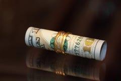 Soldi del rotolo delle banconote in dollari con i gioielli dell'oro Immagini Stock