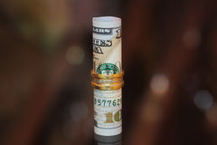 Soldi del rotolo delle banconote in dollari con i gioielli dell'oro Fotografie Stock