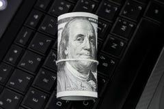 Soldi del rotolo delle banconote in dollari sulla tastiera del computer portatile Immagine Stock