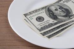 Soldi della banconota del dollaro nel piatto bianco Fotografie Stock