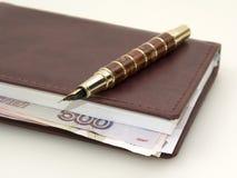 Soldi dentro il diario e penna Fotografia Stock Libera da Diritti