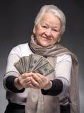 Soldi della tenuta della donna anziana in mani Immagini Stock