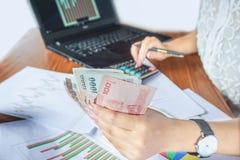 Soldi della tenuta della donna di affari mentre calcolare ed analizzare il grafico finanziario riferiscono con il calcolatore ed  Immagine Stock Libera da Diritti