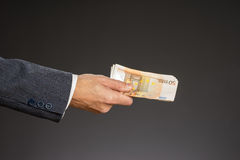 Soldi della tenuta della mano dell'uomo d'affari, euro fatture Le banconote hanno isolato il fondo grigio Fotografie Stock Libere da Diritti