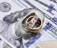 Soldi delle banconote in dollari con gli anelli dell'argento e dell'oro Fotografia Stock Libera da Diritti