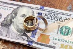 Soldi delle banconote in dollari con gli anelli dell'argento e dell'oro Fotografie Stock