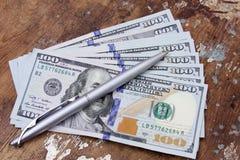 Soldi delle banconote in dollari con la penna Fotografia Stock Libera da Diritti
