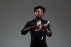 Soldi di lancio del giovane riuscito uomo d'affari africano sopra fondo scuro fotografia stock