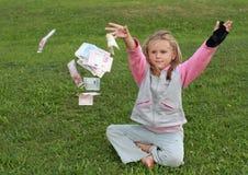 Soldi di lancio di seduta della bambina intorno Fotografia Stock Libera da Diritti